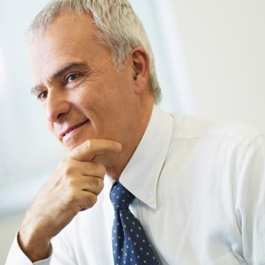 portrait of mature business man with hand on chin, looking away. Copy space